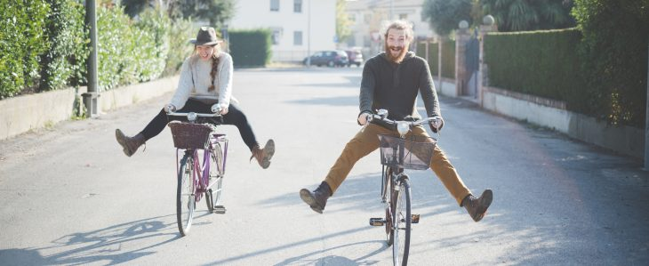 Man and woman having fun while riding bikes