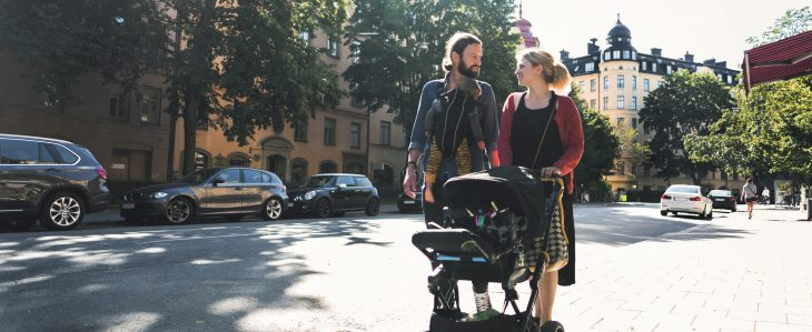 New parents walk through city streets while pushing a stroller