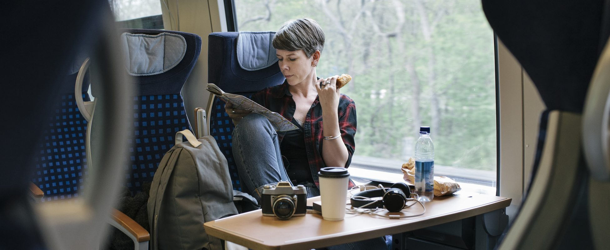 Woman travelling by train enjoys her trip while saving money